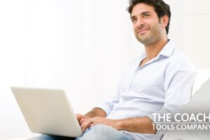 Coach considering email list on sofa with laptop