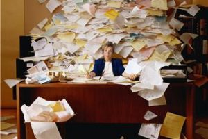 woman at desk with mountain of paper around her
