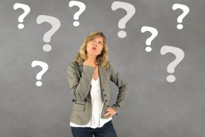 Woman wondering what the best coaching questions to ask are? Surrounded by question marks