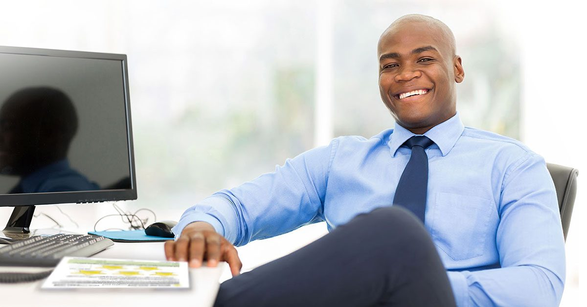 Smiling Coach with Life Coaching Exercise at Desk
