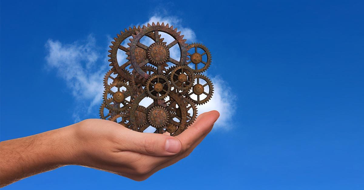 Hand Holding Metal Cogs Against Blue Sky