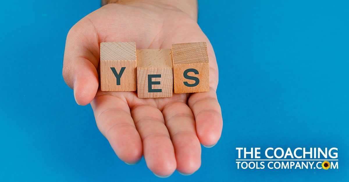 Client's Hand Saying Yes with Wooden Cubes